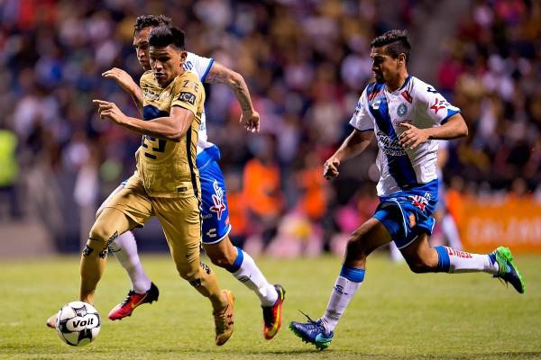 Gallardo pelea un balón con dos jugadores de Puebla