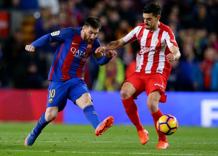 Messi realiza un pase ante la presión de un jugador del Sporting