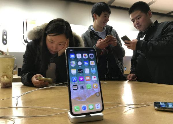 Unas personas prueban el iPhone a su llegada a Asia