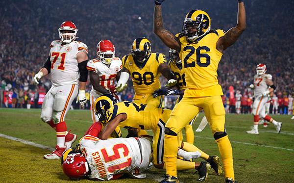 Defensiva de los Rams celebra una captura a Mahomes