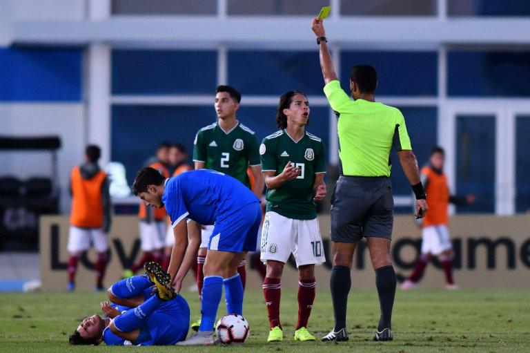 Juan Calderón muestra la tarjeta amarilla para Diego Lainez