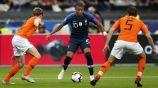 Kylian Mbappé intenta pasar entre dos defensores de Holanda