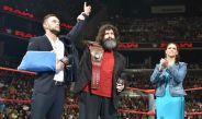 Finn Bálor (izq) entrega su título a Mick Foley (centro)
