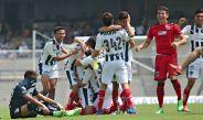 Jugador de Pumas en lamento mientras que futbolista de Rayados festejan