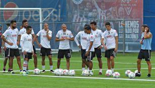 Almeyda platica con sus jugadores en un entrenamiento