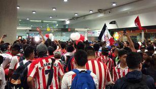 Decenas de aficionados de Chivas esperan la llegada de su equipo en aeropuerto