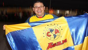 Fan del América muestra con orgullo una bandera de su equipo