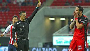 Fernando Hernández Gómez amonesta a un jugador de Xolos