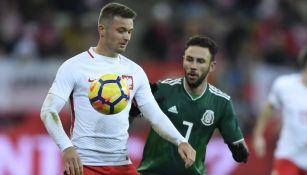 Miguel Layún disputa el balón en el partido contra Polonia