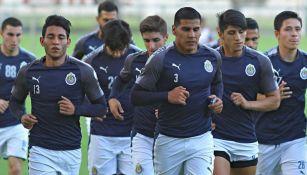 Jugadores de Chivas corren en una práctica
