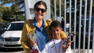 Cris Jr sosteniendo trofeos de futbol que obtuvo en la escuela