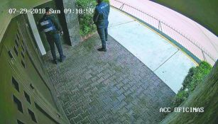 Supuestos policías esperan para entrar a un domicilio