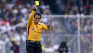 Isaac Roja muestra la tarjeta amarilla en el Pumas vs Cruz Azul del A2018
