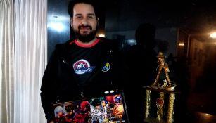 ViolentKain, posando con su joystick y el trofeo de campeón de KOF XIII que ganó en Costa Rica