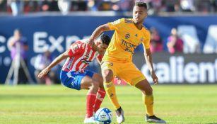 Jugadores del Atlético de San Luis y Tigres disputan un balón