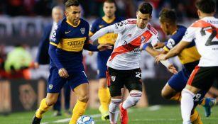Carlos Tevez disputa el balón durante el clásico contra River Plate
