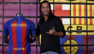 Ronaldinho posa junto a una playera del Barcelona
