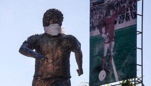 Escultura de Maradona con el cubrebocas en las afueras del inmueble