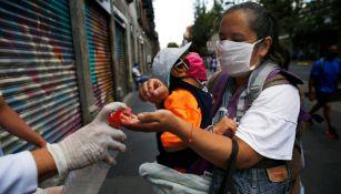 Mujer toma gel antibacterial en la CDMX