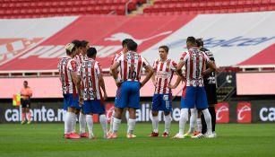 Jugadores de Chivas platican en el terreno de juego