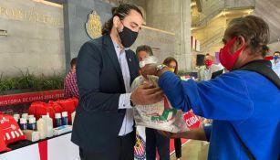 Amaury Vergara entrega los paquetes de comida a las personas