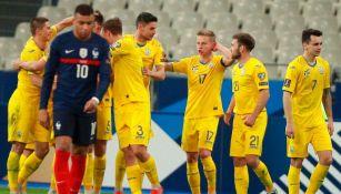 Jugadores de Ucrania festejan un gol y Mbappé se lamenta