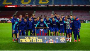 Messi y el Barcelona posando con su reconocimiento de más partidos jugados
