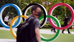 Gente camina junto a los aros olímpicos