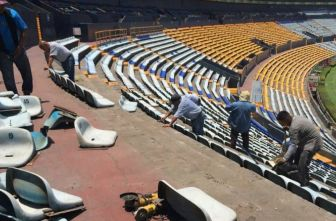 Trabajadores desmontan butacas en el Estadio Universitario