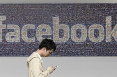 Un internauta junto al logo de Facebook