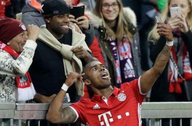Douglas Costa se toma una selfie con aficionados después de anotar con el Bayern