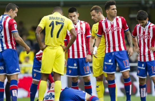 Jugadores del Gijón observan a uno de sus compañeros en el suelo