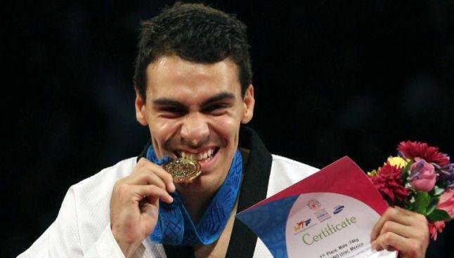 El taekwondoín Uriel Adriano muerde una medalla ganada en 2013