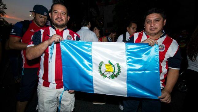 Aficionados guatemaltecos presumen una bandera de su país