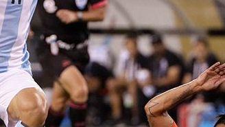 Agüero intenta quitarse una barrida de un jugador chileno