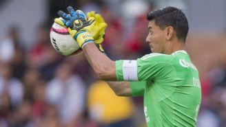 Ustari atrapando un balón en un partido de Liga MX