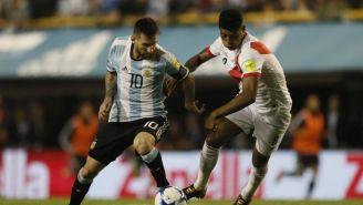 Wílder Cartagena disputa un balón con Messi en la Eliminatorias de Conmebol