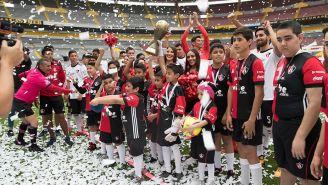Niños posan con el trofeo en el Estadio Jalisco