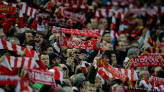 Aficionados de Liverpool levantan bufandas en Anfield