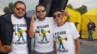 Aficionados del América posan con la playera dedicada a Pumas