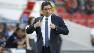 Luis Fernando Tena se acomoda el traje en partido de Liga MX