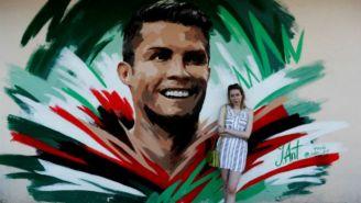 La artista rusa Julia Antipova posa frente al mural que creó de CR7