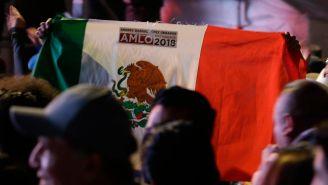 Persona lleva bandera de México con estampa de AMLO