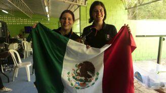 Alejandra Zavala (i) y Karen Quezada (d) portan con orgullo la bandera de México