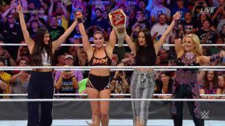 Ronda Rousey y las hermanas Bella levantando el cinturón