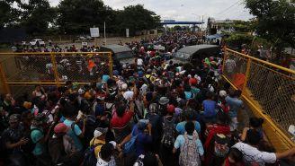 Migrantes cruzan la cerca que divide a México y Guatemala