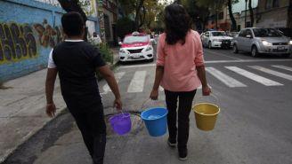 Personas cargando cubetas con agua en la Ciudad de México