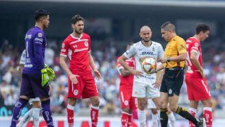 Árbitro toma el balón durante el partido