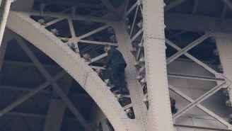 Hombre intentando escalar la torre Eiffel