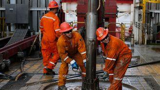 Trabajadores de Pemex colocan un taladro para perforar el suelo